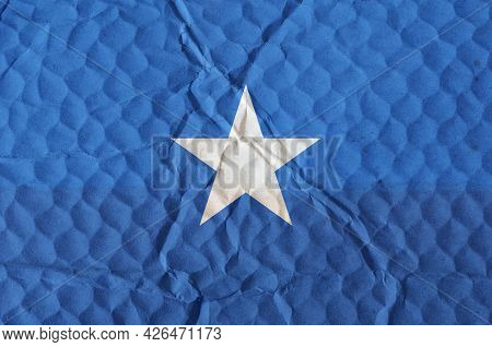 Blue Flag With White Star Of Federal Republic Of Somalia On An Uneven Textured Surface. National Fla