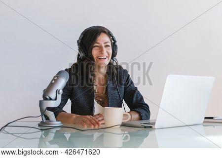Happy female radio host broadcasting live in a studio