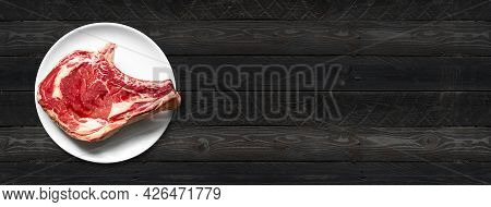Raw Beef Prime Rib And Plate Isolated On Black Wooden Background. Top View. Horizontal Banner