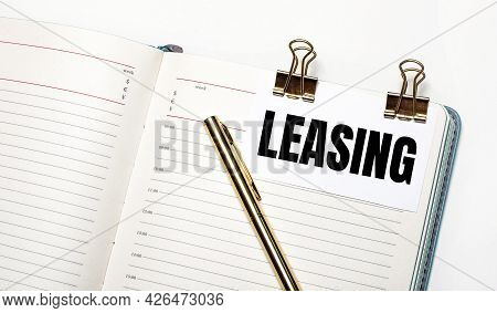 On A Light Background, An Open Notebook, A Sheet Of Paper With Gold Clips And The Text Leasing And A