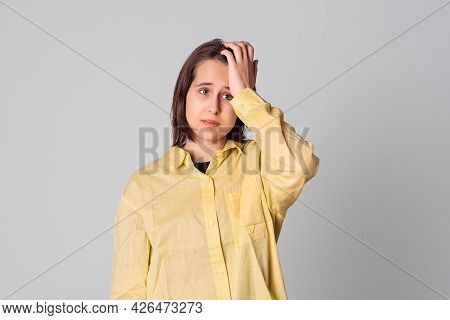 Portrait Of Puzzled Of Teen Girl Scratches Head, Dressed In Casual Yellow Shirt, Tries To Recollect