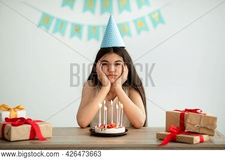 Portrait Of Disappointed Indian Teen Girl In Party Hat Sitting Alone At Table With Gifts And Birthda