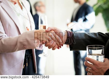 Business people shaking hands at an office party