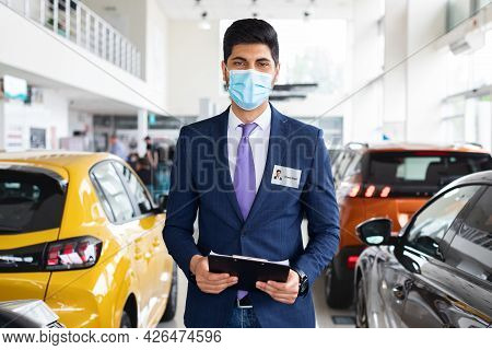 Salesman Middle-eastern Man In Face Mask Posing In Auto Showroom