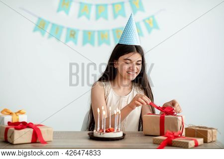 Cheerful Indian Teen Girl Wearing Festive Hat, Sitting At Table With Birthday Cake, Unpacking Gift B