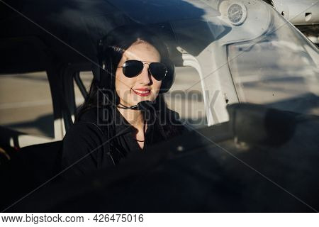Happy aviator with headphones listening to the air traffic