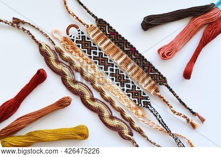 Woven Diy Friendship Bracelet With Brown Patterns Next To Skeins Of Embroidery Floss