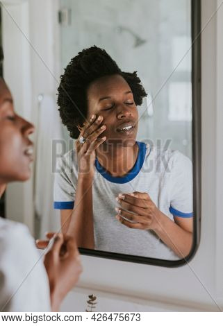 African woman standing by the mirror in the bathroom