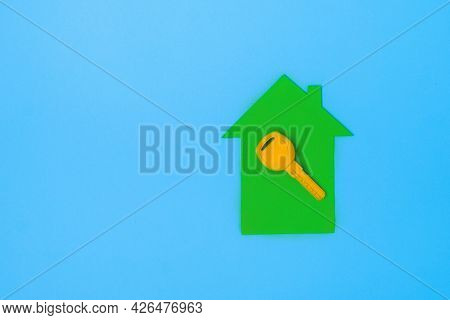 Yellow Key On A Miniature Models House. Eco House Concept. Flat Lay Top View Copy Space. Minimal Sty