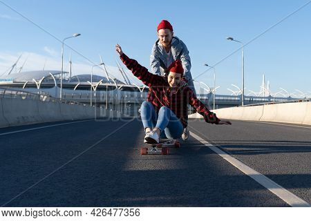 Carefree Hipsters Couple Skateboarding Together. Trendy Casual Man And Woman Have Fun Riding Longboa