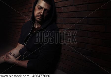 Overdosed Drug Addicted Man Near Brick Wall. Space For Text