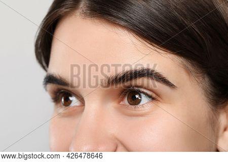 Woman After Eyebrow Tinting Procedure On Grey Background, Closeup