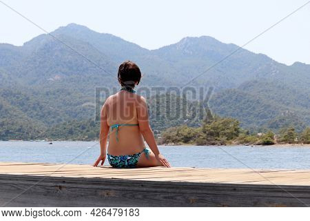 Woman In Swimsuit Sitting On Wooden Pier On Sea And Misty Mountains Background. Beach Vacation, Enjo
