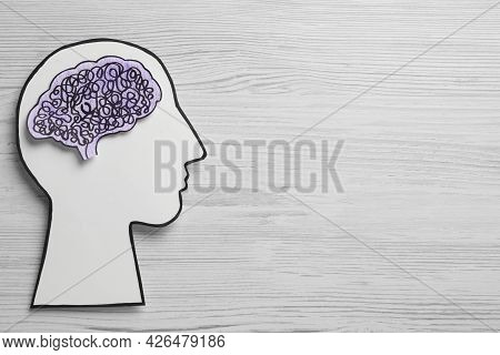 Top View Of Human Head Cutout With Brain On White Wooden Background, Space For Text. Epilepsy Awaren