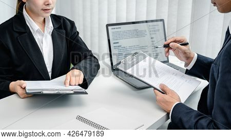 Man Employer Holding Resume Of Applicant And Asking Candidate Question While She Pointing On Resume