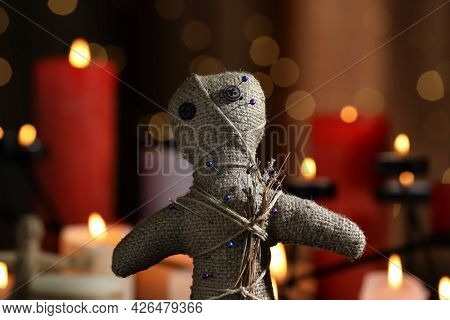 Voodoo Doll With Pins And Dried Flowers In Dark Room, Closeup. Curse Ceremony