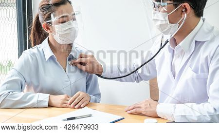 Male Doctor In Medical Mask Is Using Stethoscope To Examining Heartbeat And Symptom Of Patient While