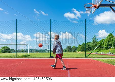 Joyful Young Boy Kid Playing Basketball On Playground.boy Performs Shot At Red Court Ball Game On Th