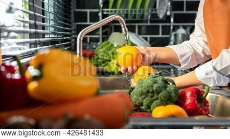 Hands Of Asian Housewife Washing Orange And Vegetables With Water In Sink While Wearing Apron And Pr