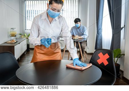 Asian Woman Waitress Wearing Face Mask And Face Shield While Wearing Gloves To Cleaning Table With A