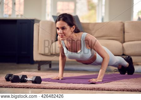 Woman In Fitness Clothing At Home In Lounge Doing Press Ups And Exercising With Hand Weights