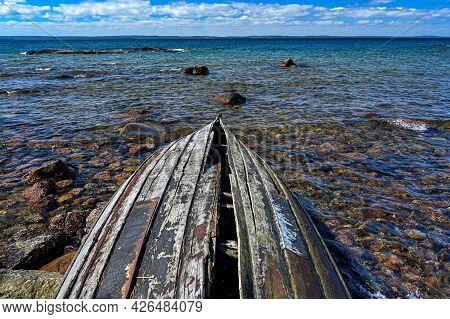 Broken Wooden Boat On Beach Of Stones