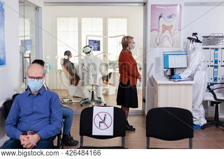 Dentist Doctor In Ppe Suit Consulting Patient In Dental Clinic Dressed In Ppe Suit As Safety Precati