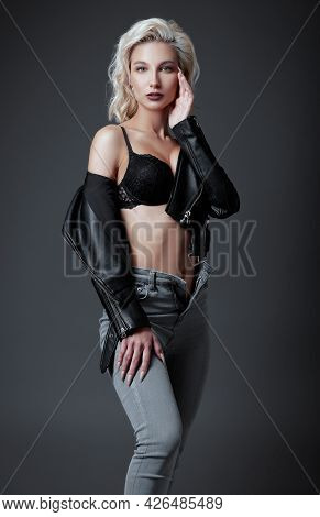Studio Fashion: Beautiful Young Woman In Black Leather Jacket, Bra And Jeans. Seductive Informal (ro