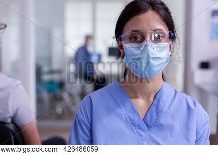 Close Up Of Tired Nurse With Protection Mask Against Coronavirus Outbreak Looking At Camera Sitting