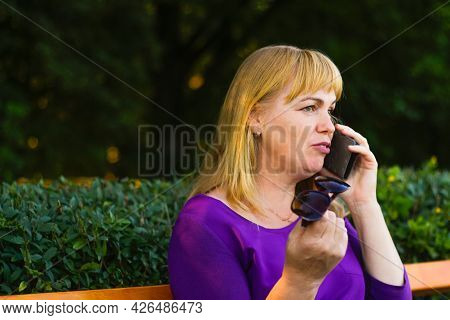 Defocus Close-up Caucasian Blond Woman Talking, Speaking On The Phone Outside, Outdoor. 40s Years Ol