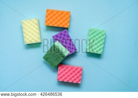 Cleaning Colorful Sponges On Blue Background. Top View Minimal Style. Spring Cleaning Concept. House