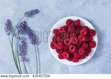 Raspberry Plate Lavender On A Gray Table Top View. Ripe Raspberries In Close-up. The Concept Of Summ