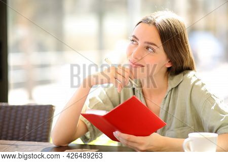 Satisfied Woman Holding Paper Agenda Wondering Looking At Side In A Coffee Shop