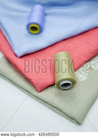 Multicolor Fabrics In Pink, Blue And Green Colors With Sewing Thread Near It In Atelier Or Drapery S