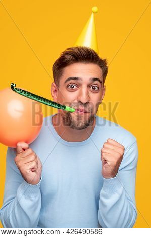 Content Bearded Male In Party Hat Holding Balloon And Congratulating On Birthday Blowing Party Horn