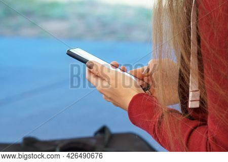 A Girl With Long Hair Holds A Phone In Her Hand