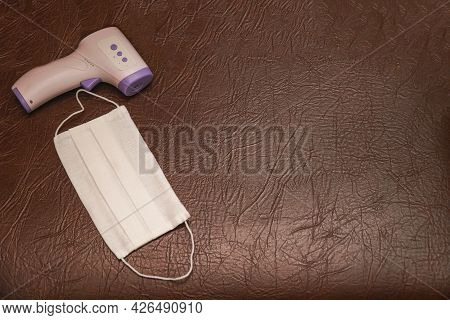 Electronic Thermometer And Protective White Face Mask On A Background Of Brown Skin
