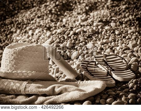 Beach Accessories On A Towel For Sunbathing. Sunny Hat And Flip Flops, Stone Rocks Sand.