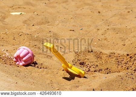 Children's Toys On The Yellow Sand. Concept Of Beach Recreation For Children. Children's Summer Game