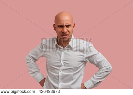 Portrait Of Crazy Bald Man With Bristle Makes Angry Grimace, Showing Tooth Grin, Hold Fists On Belt.