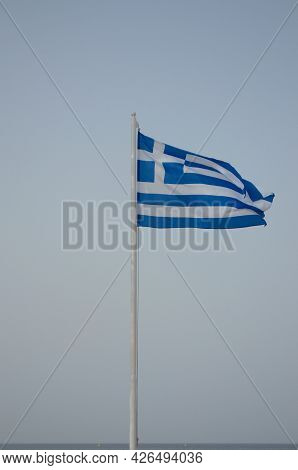 The Flag Of Greece Is Raised On The Flagpole Against The Blue Sky.