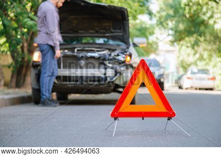 Red Triangle Warning Sign Of Car Accident On Road. Triangle In Front Of Wrecked Car And Driver Man.