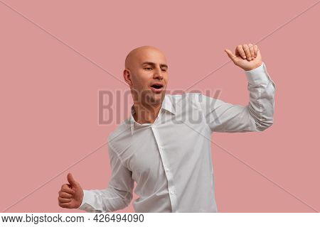 Iam A Happiest Guy. Upbeat Bald Man With Bristle In White Shirt, Keeps Arms Raised, Clenched Fists A