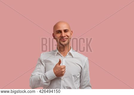 Good Work. Portrait Of Happy Bald Man With Bristle Keeps Thumb Raised, Being In Good Mood, Shows His