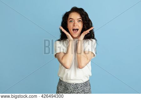 Wow, Amazed. Portrait Of Young Beautiful Curly Caucasian Woman Posing Isolated Over Light Blue Studi