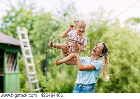 A Young Mother And Her Cute Little Girl Are Having Fun In A Sunny Garden. The Concept Of A Happy Chi
