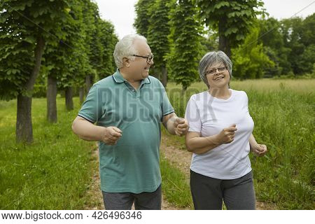Happy Active Elderly Couple On A Summer Day Jogging Outdoors In A Park Or Forest.