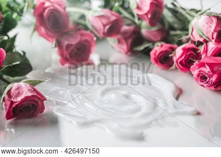 White Cream Smeared On Glossy Surface Surrounded By Blurred Delicate Pink Roses