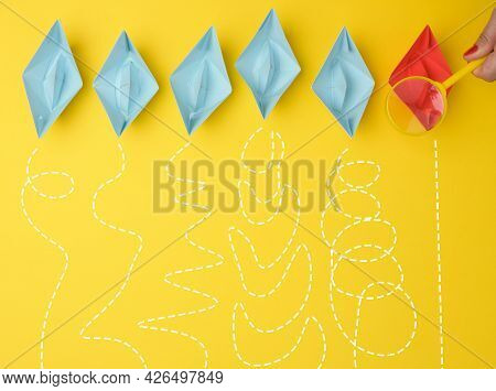 Female Hand Holds A Magnifying Glass Over A Row Of Paper Boats On A Yellow Background. Talent Search