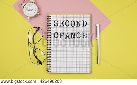 Second Chance Notice On Notepad With Pen, Glasses And Alarm Clock